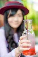 asiatisk kvinna som dricker jordgubbslimonad på ett kafé foto