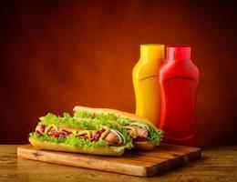två korv med senap och ketchup foto