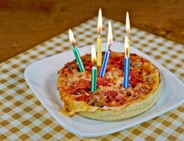 födelsedag ljus på en pizza foto