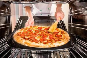 kock som lagar pizza i ugnen. foto