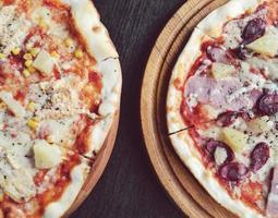 två läckra pizzor med ananas och kött foto