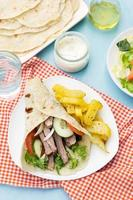 grekiska gyros med fläsk, grönsaker och hemlagat pitabröd foto