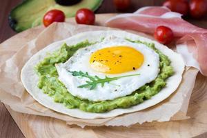 frukost med stekt ägg och sås av avokado på tortilla