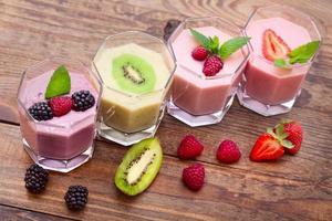 dricka smoothies sommarjordgubbe, björnbär, kiwi, hallon på träbord. foto