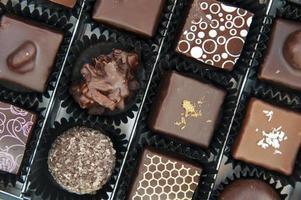 låda med olika chokladpraliner foto