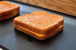 två grillade ostsmörgåsar på en varm tallrik foto