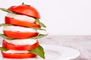 caprese sallad med mozzarella, tomat och basilika foto
