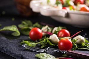 färsk tomat- och mozzarellasallad på svart skiffer foto