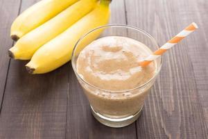 banansmoothie och färsk banan på träbakgrund foto