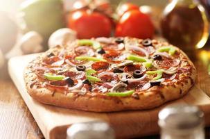 högsta italiensk pizza med pepperoni och pålägg foto