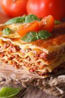 välsmakande lasagne med basilika och tomater på bordet, vertikalt foto