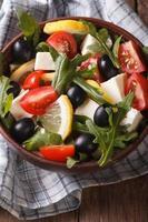 sallad av rucola, feta, oliver och tomater vertikalt ovanifrån foto