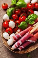 italiensk prosciutto med tomat, mozzarella och basilika foto