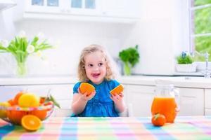 liten flicka som dricker apelsinjuice foto