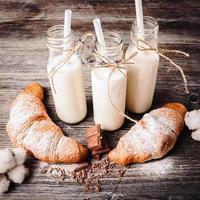 croissanter och flaskor mjölk foto