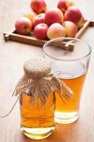glas äppeljuice med äpplen på bakgrunden. foto