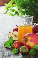 fruktjuice, mogna äpplen och jordgubbar foto