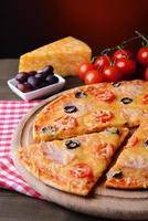 välsmakande pizza på bordet på mörkröd bakgrund foto