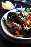 soppa med vilda musslor med vitt vin, grönsaker, salvia, koriander foto