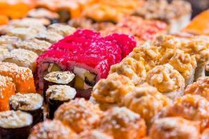 diverse sushi och rullar på träplatta i mörkt ljus foto