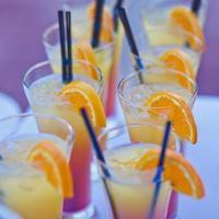rad med olika färgade alkoholcocktails på en utomhusfest