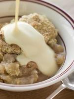 skål med äpplekrummel med vaniljsås foto