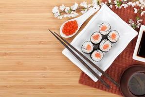 röd kaviar, sushiset, sakura gren och pinnar foto