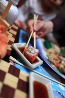 flicka tar sushi foto