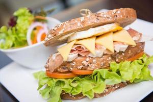 stor smörgås till lunch med parmaskinka, ägg, ost foto