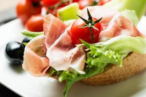 skinkasmörgås med tomat och oliv på tallriken foto