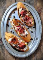 rostat bröd med karamelliserad lök, getost, jamon och grillade fikon foto