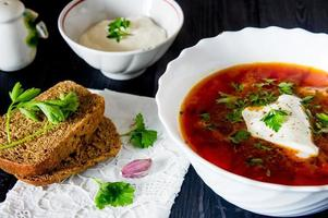 stor skål med borscht med gräddfil och örter foto