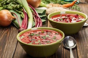rödbetasoppa med färska grönsaker i en skål foto