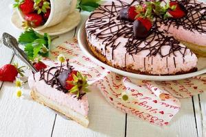 tårta glass med jordgubbar på ett träbord foto