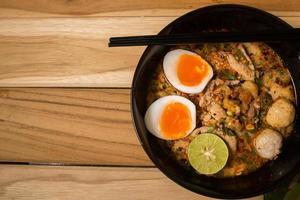 skål med nudlar med grönsaker och mjukt kokt ägg foto