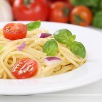 italiensk mat spagetti nudlar pasta måltid med tomater på plattan foto
