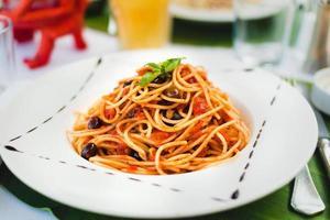 pasta med tomatsås och oliver foto