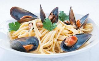 spaghetti med musslor tomat och persilja foto