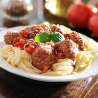 spaghetti och köttbullar med basilika garnering foto