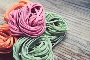 färgglad okokt italiensk pasta på träbord foto