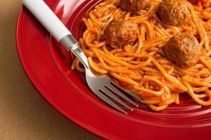 spaghetti och köttbullar på en röd maträtt med gaffel. foto