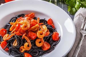 svart spaghetti med räkor och tomat. foto