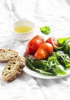 färsk basilika, tomater, olivolja och en baguette foto