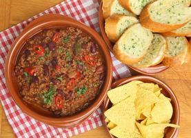 chili med vitlöksbröd och tortillachips foto