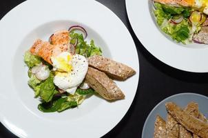 lax sallad med ägg benedict, serveras med baguette foto