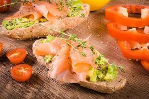 frukost: avokadostost med lax på träbakgrund. foto