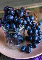 kvist av blå druvor i ett glas på en tallrik, vertikalt foto