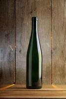 enkel vinflaska framför träväggen foto