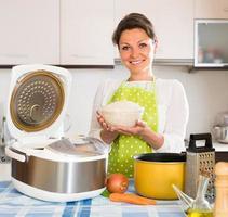 kvinna matlagning med multicooker hemma foto