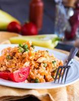 risotto med kyckling och grönsaker på en tallrik med gaffel foto